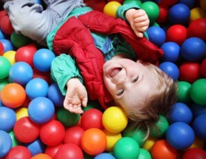 Two year old boy in a pool of coloured balls